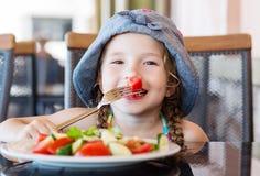 Het gelukkige peutermeisje eten stock afbeeldingen