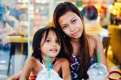 Het gelukkige plakken van twee zusters in een koffie, zusters die in koffie-winkel koelen Royalty-vrije Stock Foto's
