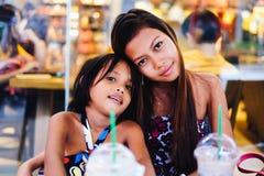 Het gelukkige plakken van twee zusters in een koffie, zusters die in koffie-winkel koelen Royalty-vrije Stock Afbeelding