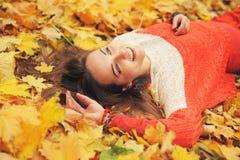 Het gelukkige portret van de vrouwenherfst, die in de herfstbladeren liggen Royalty-vrije Stock Foto's