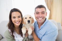Het gelukkige puppy van de paarholding thuis Stock Afbeeldingen