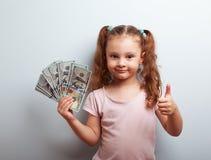 Het gelukkige rijke de holdingsgeld van het jong geitjemeisje en het tonen van duim ondertekenen omhoog Royalty-vrije Stock Afbeelding