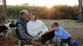 Het gelukkige rijpe paar op picknick met kleinzoon en huisdier zit bij plaid met laptop op achtergrondzonsopgang stock videobeelden
