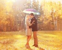 Het gelukkige romantische kussende paar in liefde met kleurrijke paraplu samen bij warme zonnige dag over het gele vliegen doorbl stock foto's