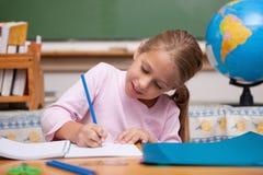 Het gelukkige schoolmeisje schrijven stock foto's