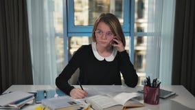 Het gelukkige schoolmeisje spreekt op smartphone Overleg met de leraar Het doen van thuiswerk Hij glimlacht stock video