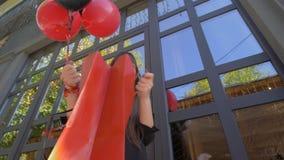 Het gelukkige shopaholic meisje tijdens zwarte Vrijdag kijkt verbaasd in zak en gelukkig glimlachen met ballons stock video