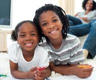Het gelukkige siblings trekken die op de vloer ligt Stock Foto's
