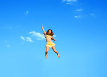 Het gelukkige springende meisje op een achtergrond van het blauw Stock Fotografie