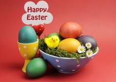 Het gelukkige stilleven van Pasen tegen een rode achtergrond met teken. Royalty-vrije Stock Afbeeldingen