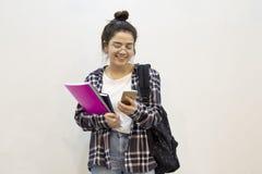 Het gelukkige student texting met telefoon stock foto