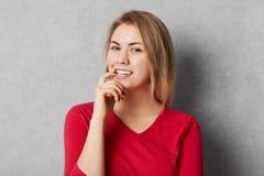 Het gelukkige tevreden vrouwelijke model gekleed in rode kleren, kijkt met zekere uitdrukking, over grijze achtergrond, modellen  stock afbeeldingen