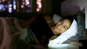 Het gelukkige tiener doorbladeren en het letten op media in een tablet in het bed stock footage