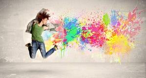 Het gelukkige tiener springen met kleurrijke inkt ploetert op stedelijke backg Stock Fotografie