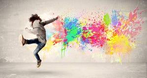 Het gelukkige tiener springen met kleurrijke inkt ploetert op stedelijke backg Royalty-vrije Stock Afbeelding