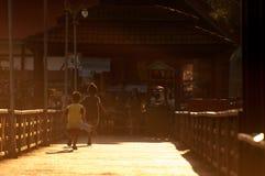 Het gelukkige twee kinderensilhouet spelen in werking gesteld in brug op avondlicht Stock Foto