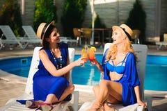 Het gelukkige twee meisjeszon baden dichtbij de pool op ligstoelen royalty-vrije stock afbeeldingen