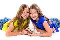 Het gelukkige tweeling de meisjes en het puppyhond van het zusterjonge geitje liggen Stock Foto