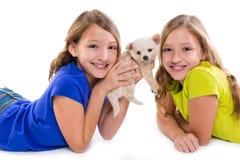 Het gelukkige tweeling de meisjes en het puppyhond van het zusterjonge geitje liggen Royalty-vrije Stock Afbeelding
