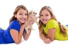 Het gelukkige tweeling de meisjes en het puppyhond van het zusterjonge geitje liggen Royalty-vrije Stock Fotografie