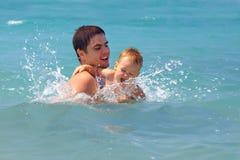 Het gelukkige vader en baby spelen in overzees water Royalty-vrije Stock Afbeeldingen
