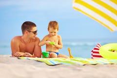 Het gelukkige vader en jong geitje spelen op het strand Royalty-vrije Stock Foto
