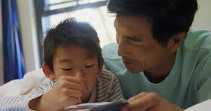 Het gelukkige vader en zoonsboek van het lezingsverhaal op bed 4k stock videobeelden