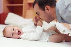 Het gelukkige vader spelen met baby in bed Stock Afbeeldingen
