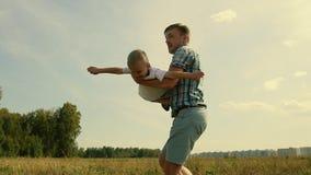 Het gelukkige vader spelen met zijn zoon die hem oprapen in zijn wapens De jongen veronderstelt hij als een vliegtuig vliegt stock video