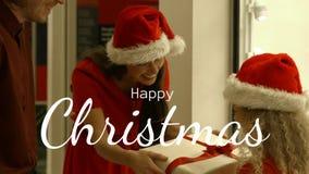 Het gelukkige van de van de Kerstmistekst en moeder en vader aanwezige geven aan haar dochter stock footage