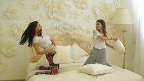 Het gelukkige van het familiemoeder en kind dochter spelen op bed en hoofdkussenstrijd stock footage