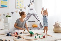 Het gelukkige van het familiemoeder en kind zoon spelen in stuk speelgoed spoorweg in pl royalty-vrije stock afbeelding
