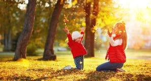 Het gelukkige van het familiemoeder en kind meisje spelen en werpt bladeren in a Royalty-vrije Stock Afbeeldingen