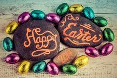 Het gelukkige van letters voorzien van Pasen 2017 geschreven op kiezelstenen met chocolade b.v. Royalty-vrije Stock Foto's