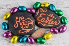 Het gelukkige van letters voorzien van Pasen 2017 geschreven op kiezelstenen met chocolade b.v. Royalty-vrije Stock Foto