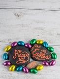 Het gelukkige van letters voorzien van Pasen 2017 geschreven op kiezelstenen met chocolade b.v. Royalty-vrije Stock Afbeelding