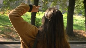 Het gelukkige verbazende Kaukasische meisje met lang haar bekijkt zon en geniet van het op haar gezicht terwijl status in groen stock footage