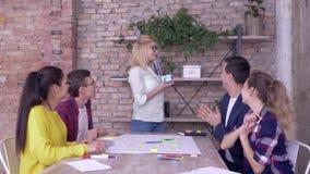 Het gelukkige verjaardags chef-, jonge team van creatieve werknemers wenst de gelukkige vakantie van de vrouwenmentor geluk en ge stock footage