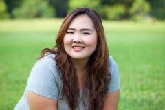 Het gelukkige vettige Aziatische vrouw openlucht stellen stock fotografie