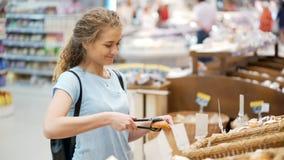 Het gelukkige volwassen meisje neemt broodjes met tang in toevallige minimarket op stock footage