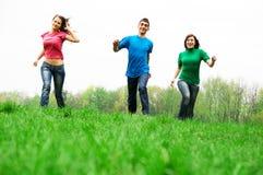 Het gelukkige vrienden springen Stock Foto's
