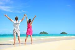 Het gelukkige vrije paar die van het de zomerstrand op reis toejuichen Stock Foto