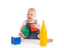 Het gelukkige vrolijke kind spelen met blokkenkubussen op wit stock afbeeldingen
