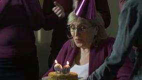 Het gelukkige vrouw blazen uit schouwt op cake en het maken van wens, verjaardag 90 die, pret hebben stock video