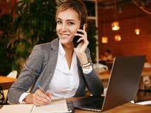 Het gelukkige vrouw gebruiken die met mobiele en gebruikslaptop computer babbelen royalty-vrije stock fotografie