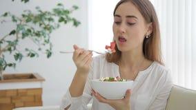 Het gelukkige vrouw ontspannen op bank die salade in woonkamer eten stock footage