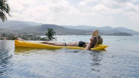 Het gelukkige vrouw ontspannen op een gele opblaasbare matras in zwembad stock videobeelden