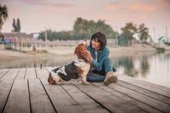 Het gelukkige vrouw spelen met haar hond door de rivier stock afbeeldingen