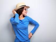 Het gelukkige vrouw stellen in profiel in glazen en strohoed op blauwe B Stock Foto
