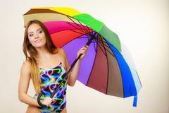 Het gelukkige vrouw stellen in zwempak en kleurrijke paraplu royalty-vrije stock fotografie